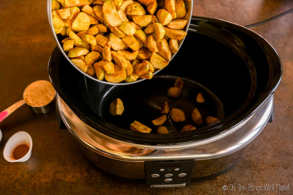 Pouring apple pieces into a slow cooker