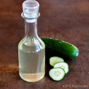 homemade cucumber extract in a bottle near a cucumber and some cucumber slices.