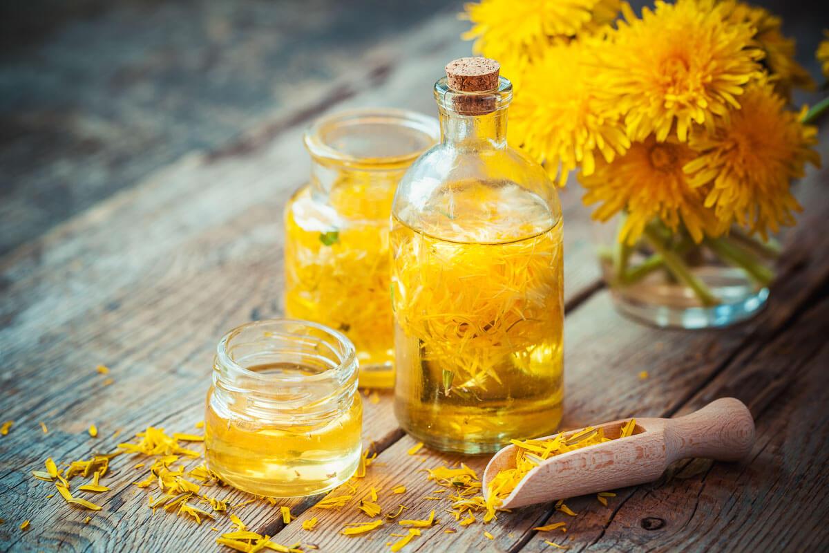 several bottles of oil with dandelion petals