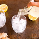 pouring ginger beer into a glass with ice