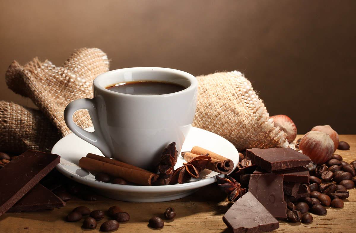 coffee surrounded by cinnamon sticks, star anise, chocolate pieces, and coffee beans.