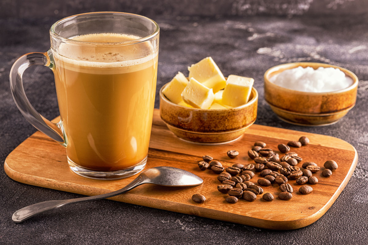bulletproof coffee next to bowls of butter, solid oil, and coffee beans