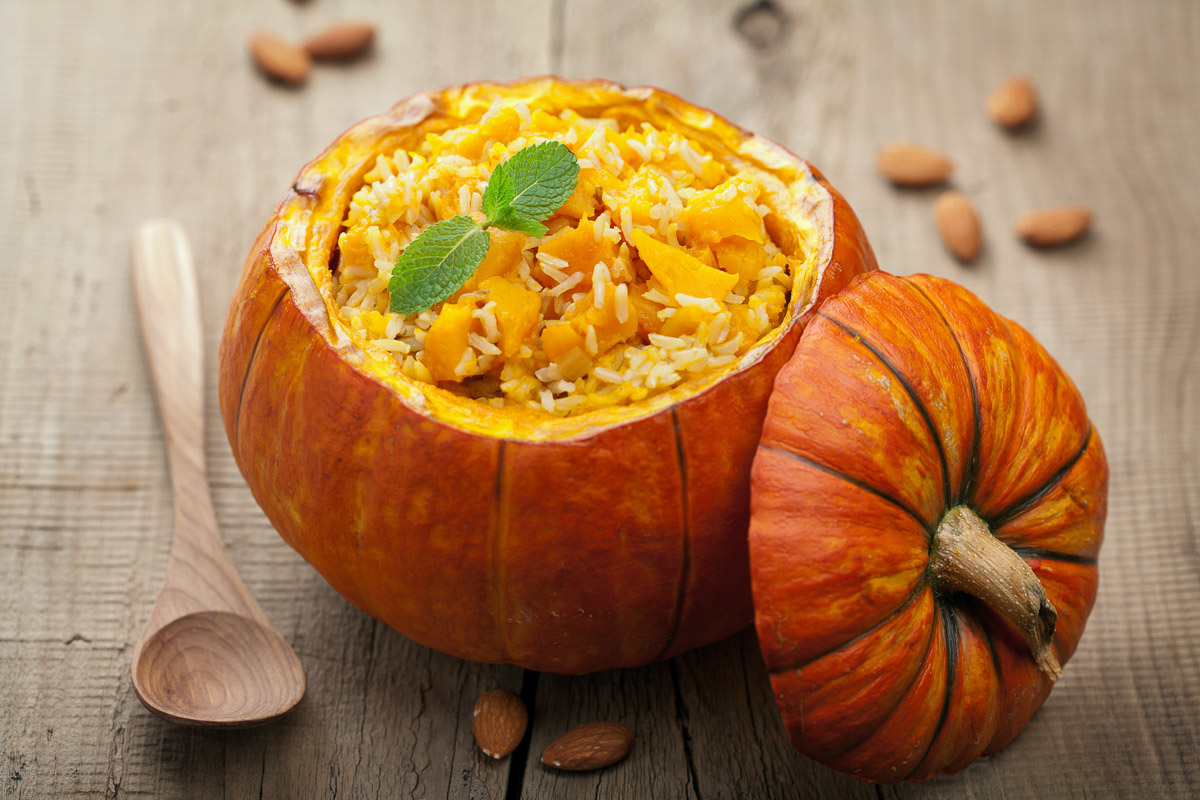 A hallowed out pumpkin being used as a bowl for a vegetable rice dish.