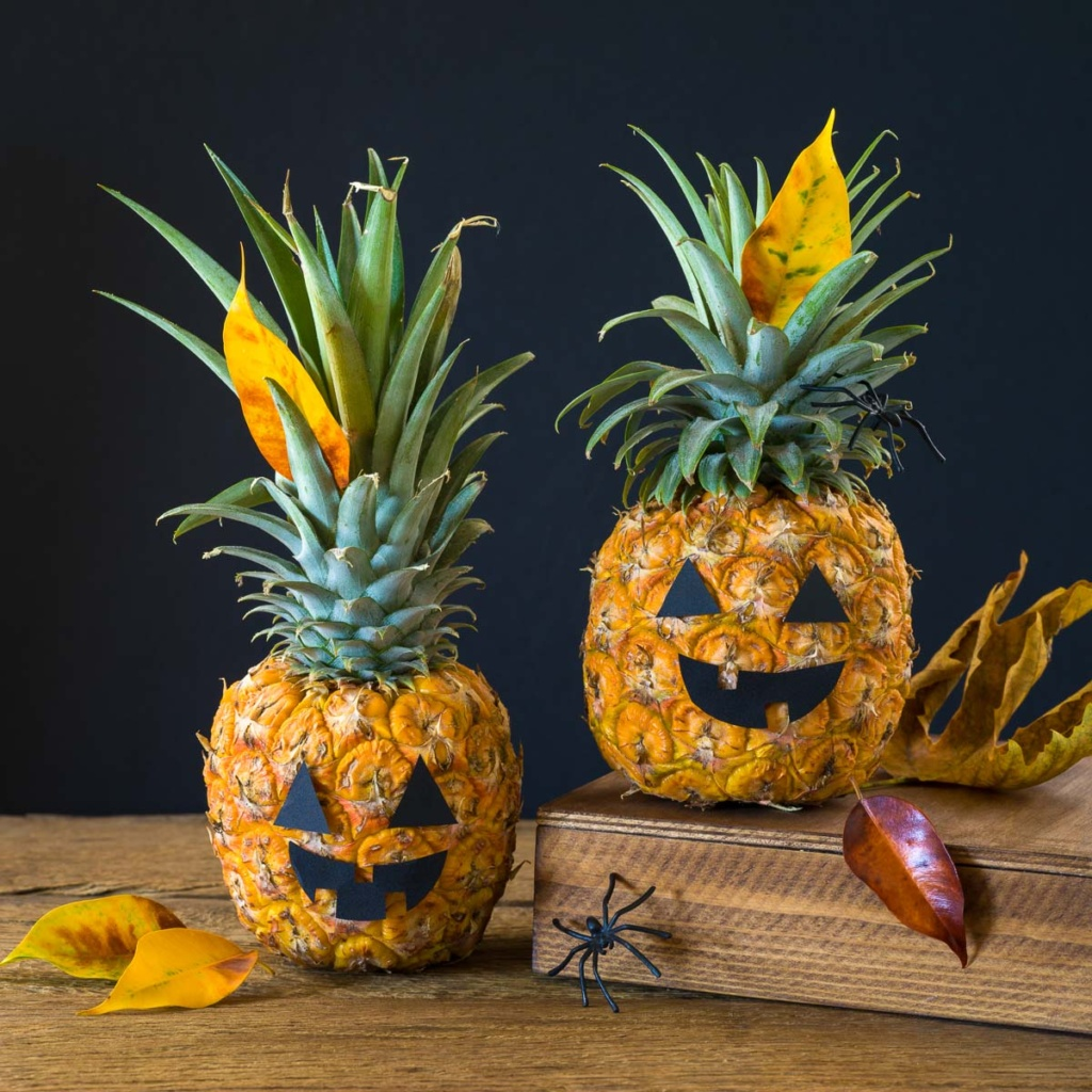 pineapples decorated with paper eyes and mouth to look like jack-o-lanterns